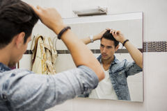 Reflection of Man Bushing Hair in Mirror. Reflection of Young Man Bushing Hair in Mirror Getting Ready to Go Out Stock Images