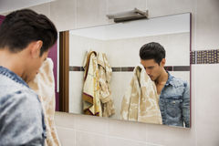 Reflection of Man Drying Face with Towel in Mirror. Reflection of Young Man Drying Face with Towel in Mirror as Part of Daily Hygiene Routine royalty free stock photos