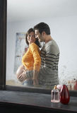 Reflection Of Man Embracing Pregnant Woman Stock Images