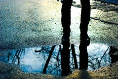 Reflection of man standing near puddle stock photo