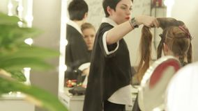 Reflection in mirror haircutter combing female hair during haircutting in beauty salon. Hairdresser making female stock footage