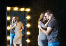 Reflection in a mirror of happy couple expecting the baby. Couple husband and pregnant wife near the brick wall in an empty room stock images