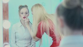 The reflection in the mirror make-up work. Makeup artist paints lips stock footage