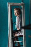Reflection in the mirror modest Beautiful blond bride in white negligee sitting on the black wrought iron stairs. Reflection in the mirror Beautiful blond bride Royalty Free Stock Images