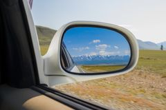 Reflection in the mirror of a riding white car of large altai mo royalty free stock image