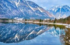 The bank of Obertraun, Hallstatter see, Salzkammergut, Austria. Reflection in mirror surface of Hallstatter see lake of the snowy bank of Obertraun village stock image