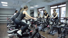 Reflection in mirror three women on stationary bike in gym. Brunette woman with long picked tail hair white t-shirt, grey pants, white sneakers pedaling in stock footage