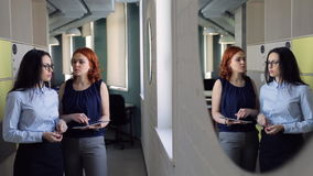 Reflection in mirror of two women discussing topics inside office. Redhead woman with curly hair shows in tablet Important information explains to colleague stock footage