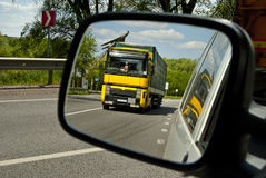 Reflection in the mirror yellow truck passing car. Stock Image