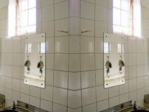 REFLECTION OF MIRRORED URINALS stock photography