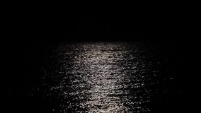 Reflection of the moon in seawater, a long path of moonlight reflected in the water.  stock footage