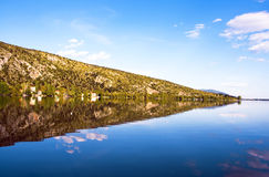Reflection mountain into the lake (Makedonia,Greec. E)  with blue sky Royalty Free Stock Images