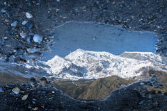 Reflection of a mountain in a puddle. Reflection of Dhaulagiri mountain range in a puddle close to Larjung village in Nepal royalty free stock photography