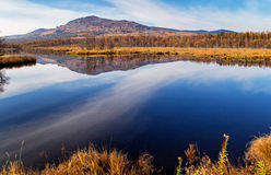 Reflection of mountain and sky in blue water Stock Photography