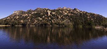 The reflection of the mountain in the water at the Granite Basin Recreation Area in Prescott, Arizona, USA. With blue skies overhead royalty free stock photo