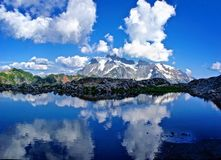 Reflection of Mountains and Clouds in Alpine Lake Stock Images
