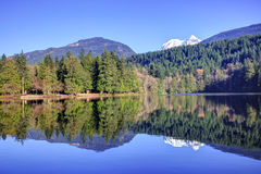 Reflection of mountains and forest in Alice lake royalty free stock image