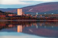 Reflection of mountains and industrial buildings in the lake at sunset. Norilsk Talnakh. Reflection of mountains and industrial buildings in the lake at sunset stock photo