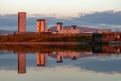 Reflection of mountains and industrial buildings in the lake at sunset. Norilsk Talnakh. Reflection of mountains and industrial buildings in the lake at sunset stock images