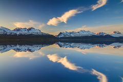 Reflection of of mountains in the Norwegian fjord at sunset Stock Image