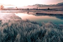 Reflection of mountains with snowy peaks. In the mirror of the lake in the early morning stock photos