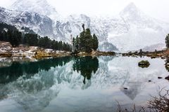 Reflection of mountains with snowy peaks. In the mirror of the lake royalty free stock photos