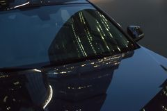 Reflection of multi-storey buildings on the hood of the car at n Royalty Free Stock Image