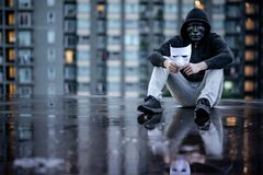 Reflection of mystery hoodie man with black mask holding white mask sitting in the rain on rooftop of abandoned building. Bipolar. Disorder or Major depressive royalty free stock photo