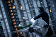 Reflection of mystery hoodie man with black mask holding white mask sitting in the rain on rooftop of abandoned building. Bipolar. Disorder or Major depressive stock photography