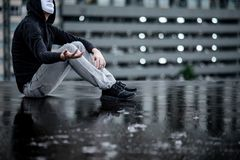 Reflection of mystery hoodie man in white mask sitting in the rain on rooftop of abandoned building. Bipolar disorder or Major. Depressive disorder. Depression stock image