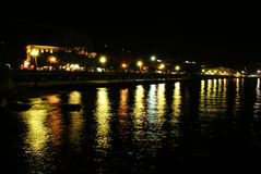 Reflection of the night lights of the embankment from water in bay Stock Images