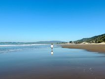 Reflection on Northern Californian Stinson Beach. Woman walking without leaving footprints on  beach in northern California with a reflection in the wash of the Stock Image