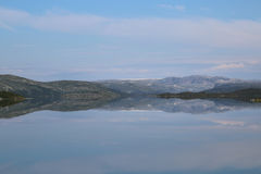 Reflection on Norwegian Lake. Reflection of mountains and blue sky in a completely still lake royalty free stock images