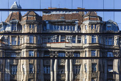 Reflection of old architectural building in the windows of a mod Royalty Free Stock Image