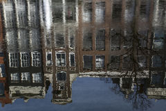 Reflection of old brown european buildings in the frozen water. In the day in winter Royalty Free Stock Image