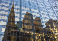 Reflection of old brown stone church and building in the glass o Stock Photo