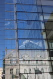 Reflection. Old buildings reflectd in modern glass building Stock Image