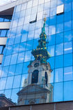 Reflection of old church in modern building. Windows, Stiftskirche, Mariahilferstrasse, Vienna Stock Photography