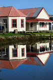 Reflection of old ruin houses on a Awanui river NZ Stock Image