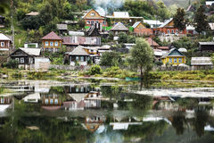 The reflection. The old village on the shore of the pond. Royalty Free Stock Photography