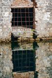 Reflection of an old window with a grate in the water. Fortress wall of Kotor, Montenegro stock photo
