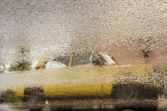 Reflection of old yellow car on wet asphalt during rain Stock Image