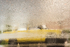 Reflection of old yellow car on wet asphalt during rain Stock Images