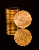 Reflection of one ounce gold coin black stock image