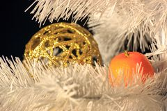 The reflection of the orange tangerine to Golden on the Christmas tree, both items are on eating white. decorations before royalty free stock photography