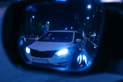 Reflection of overtaking car in rearview mirror. Dark night. Blurred background Royalty Free Stock Photos