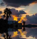 Reflection of a palm silhouette under a cloudy sky. At sunset in Sardinia Stock Photos