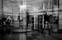 Reflection of people in a building. Photo trough the glass frontage Stock Image