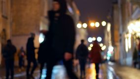 Reflection people rain evening. Reflection silhouettes of unrecognizable people on wet pavement in streetlights stock video footage