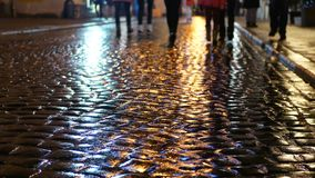 Reflection people rain evening. Reflection silhouettes of unrecognizable people on wet pavement in streetlights stock video